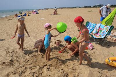Детки закапываются в песке на пляже
